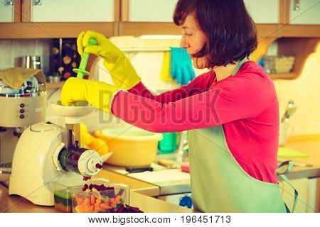 Woman adding different vegetables red and green in juicer maker. Housewife in kitchen making raw juice preparing nutritious vitamin packed drink. Healthy eating vegetarian food dieting concept