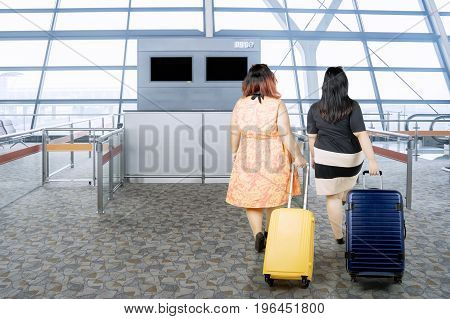Back view of two fat women with suitcases while walking in the terminal airport