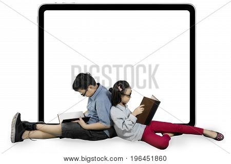 Two nerdy students reading a book while sitting near an empty whiteboard isolated on white background