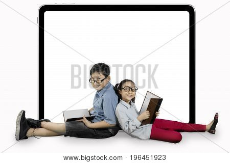 Image of two elementary students is learning with book and sitting near a blank billboard in the studio