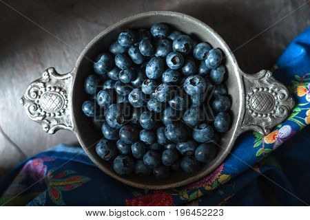 Tin bowl with blueberries, colored napkin on slate horizontal