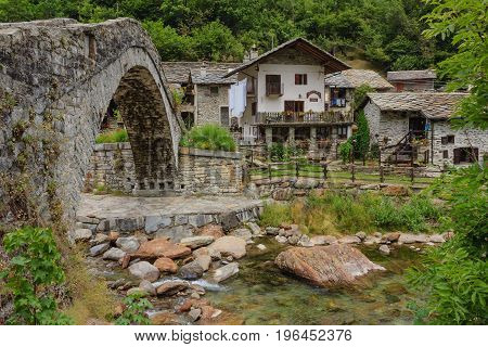 a romanesque bridge made of donkey back of the century 1700, typical Piedmontese which  leads to the characteristic alpine village of Fondo made of stone houses with the stone roofs