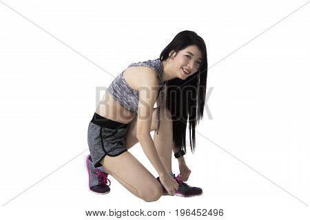 Young Asian woman with slim body tying shoelaces in studio isolated on white background
