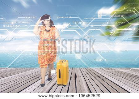 Overweight woman going to holiday and using virtual reality glasses at pier to choose her destination while carrying a suitcase