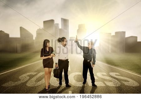 Group of three young business people giving high five while standing on the road with a word of success