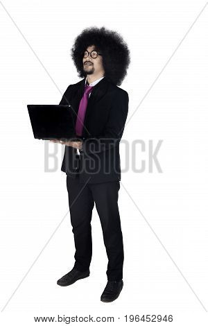 Full length of young businessman wearing formal suit and using a laptop computer while standing in the studio