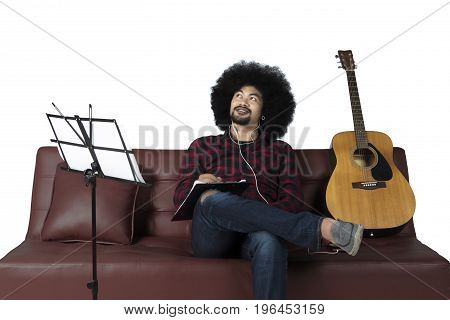 Young man composing a song and listening music with earphone while sitting on sofa isolated on white background