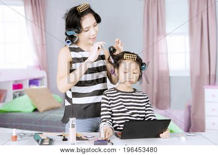 Pretty young mother curling hairs her daughter with rollers while doing makeup in the bedroom