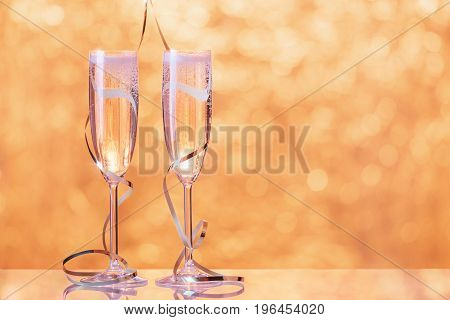 Two full champagne glasses wrapped with ribbon as a decoration