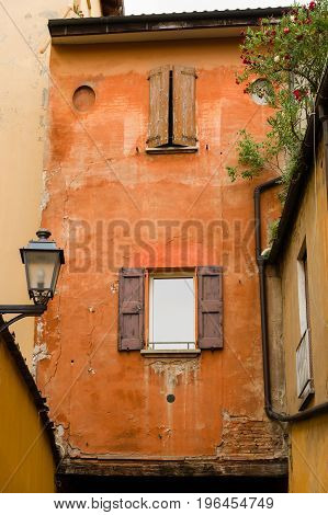 Red Facade Of Hold House In Bologna City Centre With Wooden Window Shutters
