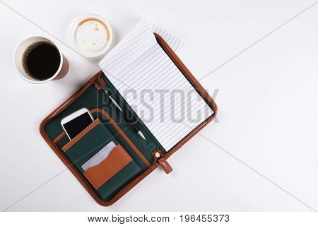 High angle shot of a white business desk, with coffee, note pad and other office equipment.