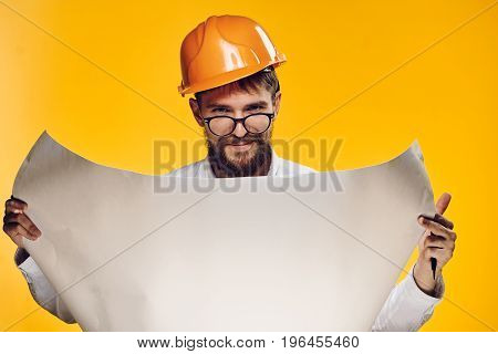 Engineer with a beard on a yellow background holds blueprints.