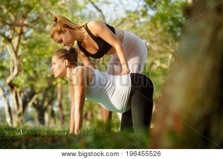 Mom with back pain mother during pregnancy. Prenatal lesson in city park antenatal class outdoor. Yoga teacher midwife personal trainer counselor doctor teaching exercise to pregnant woman