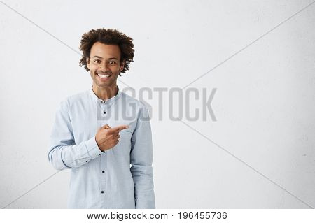 Advertising Concept. Horizontal Portrait Of Dark-skinned Happy Male Dressed In White Shirt Pointing