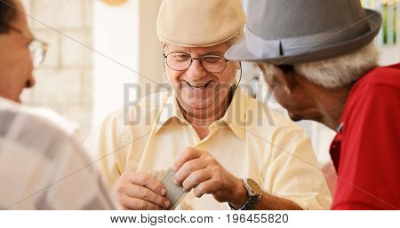 Group Of Happy Seniors Playing Cards Game
