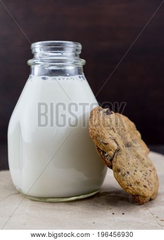 Single Chocolate Chip Cookie Leaning Against Jar of Milk in Vintage Bottle