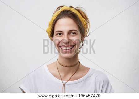 Cheerful Beautiful Young Female With European Appearance Wearing Yellow Headband, White T-shirt And
