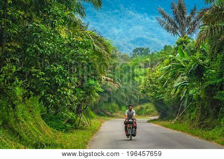 Male cyclist cycling through dense jungle landscape of Sumbava island, Indonesia