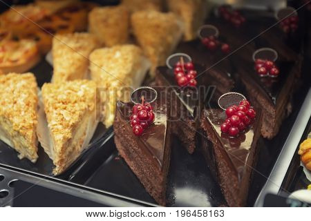 Fridge with cakes in shop, closeup