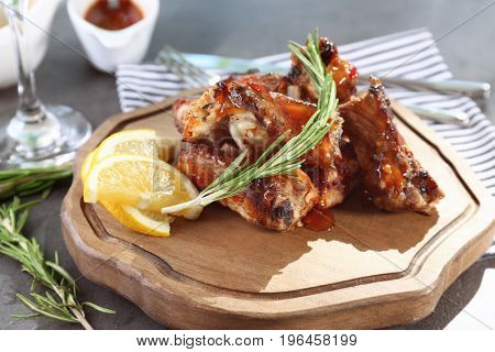 Wooden board with delicious pork ribs on table, closeup