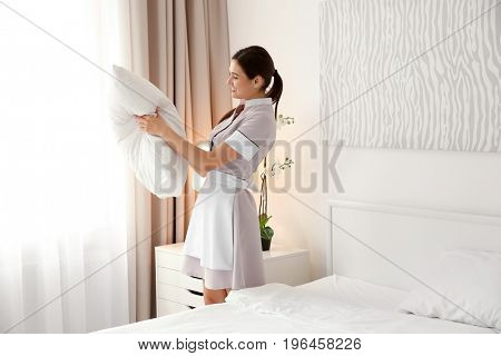 Young maid making bed in light hotel room