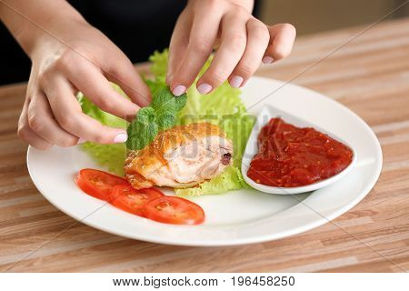 Female hands adding mint leaves to yummy fried chicken thigh with sauce on white plate