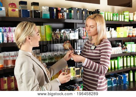 Young woman and assistant choosing perfume at store