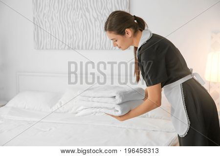 Young maid holding stack of towels near bed in hotel room