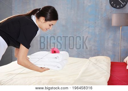 Young maid putting stack of towels with flower on bed in light hotel room