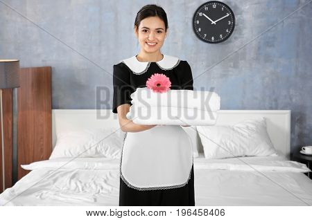 Young maid holding stack of towels with flower in light hotel room