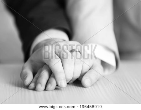 Gay couple holding hands together, closeup. LGBT rights concept