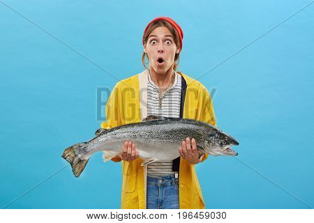 Portrait Of Shocked Female With Widely Opened Eyes And Mouth Holding Huge Fish Which Her Husband Cau