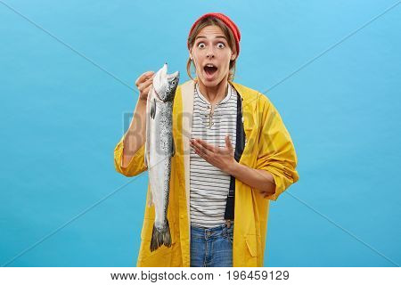 Just Have Look At This! Shocked Female Angler In Yellow Anorak And Red Hat Demonstrating Very Long,