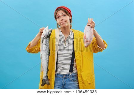 Young Female Angler Looking With Doubts At Camera While Holding Two Fish Going To Buy One Of Them, N