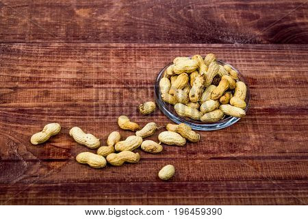 peanuts in shells with fresh groundnut on wooden on nature background
