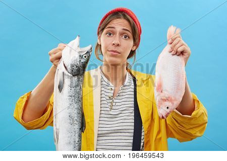 Studio Shot Of Young Female Dressed Casually Holding Two Fish In Hands, Demonstrating Catch Of Her H