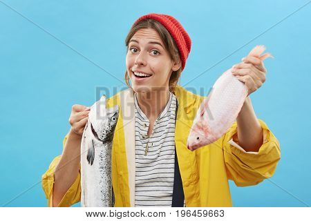 Confused Happy Female In Red Hat, Yellow Raincoat And Sweater Holding Two Fish Not Knowing What To C