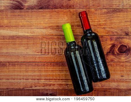 Top view of two wine bottles on a rustic wood table with copy space.