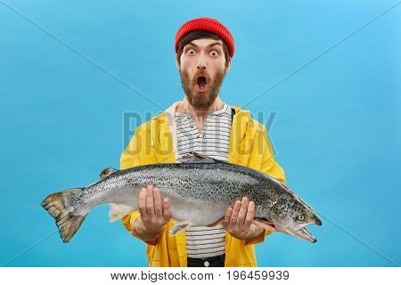 Studio Shot Of Stylish Young Bearded Fisherman In Yellow Raincoat And Red Hat Looking In Shock With