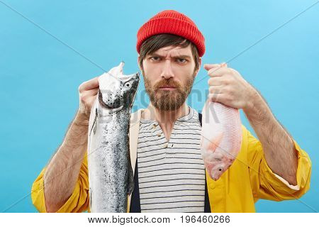 Look What I've Caught! Studio Portrait Of Grumpy Serious Young Fisherman With Beard Holding Two Fres