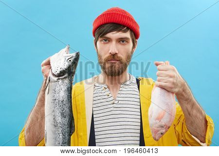 Confident Successful Young Unshaven Fisherman In Cloak And Hat Demonstrating His Catch After Long Ho