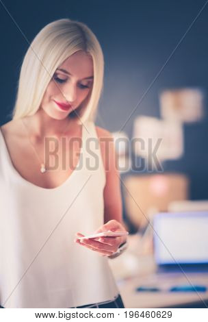 Woman designer using on mobile phone in office.