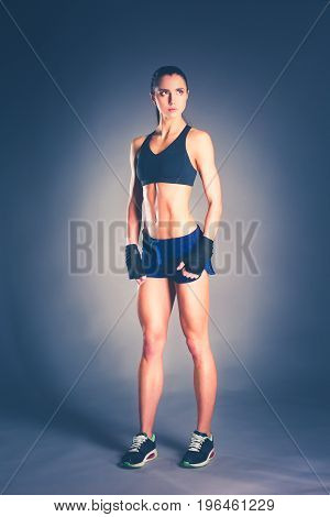 Muscular young woman posing in sportswear against black background
