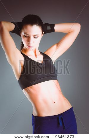 Muscular young woman posing in sportswear against black background.