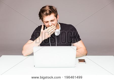 Young Man Working At Laptop And Yawn