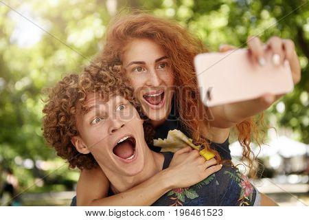 Joyful Couple Spending Time Together: Red-haired Freckled Female And Curly Handsome Guy Making Grima