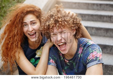 Funny Freckled Female With Reddish Bushy Hair Scratcing Head Of Her Friend Who Is Closing Eyes And O