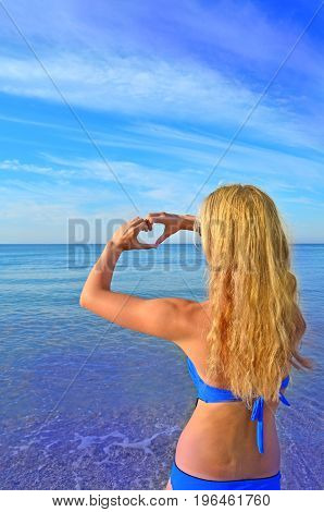 Blonde Young Woman Making Heart With Her Hands