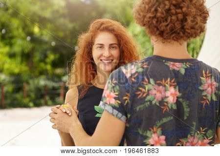 Togetherness And Love Concept. Happy Freckled Woman With Long Curly Red Hair Dancing Outdoors With H