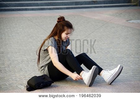 Beautiful young girl has fun repairing shoes sitting on pavement cobblestone